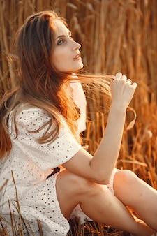 Mooi meisje in een witte jurk. vrouw in een de herfstgebied. dame in een strooien hoed.