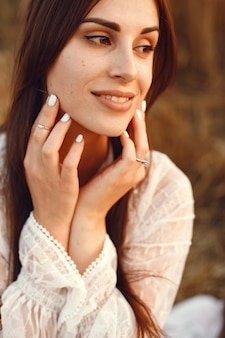 Mooi meisje in een witte jurk. vrouw in een de herfsttarweveld.