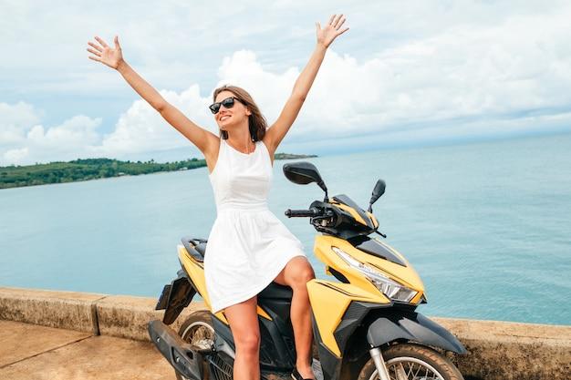 Mooi meisje in een witte jurk zit op een scooter op blauwe zee achtergrond. portret van vrouwelijke fietser voelt zich vrij en zelfstandig zittend op een bromfiets