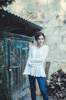 Mooi meisje in een witte kanten blouse en spijkerbroek in de buurt van het huis van de boer