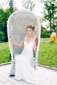 Mooi meisje in een witte stoel in de natuur. blond in een jurk met een diepe halslijn.