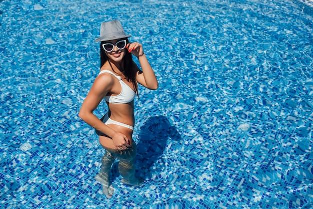 Mooi meisje in een witte zwembroek, zonnebril en hoed met een mooie figuur badend in het zwembad