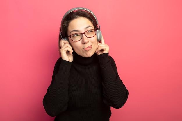 Mooi meisje in een zwarte coltrui en bril met koptelefoon opzij kijken blij en positief tong uitsteekt