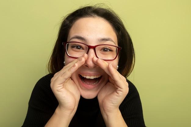 Mooi meisje in een zwarte coltrui en glazen blij en opgewonden schreeuwen met handen in de buurt van mond