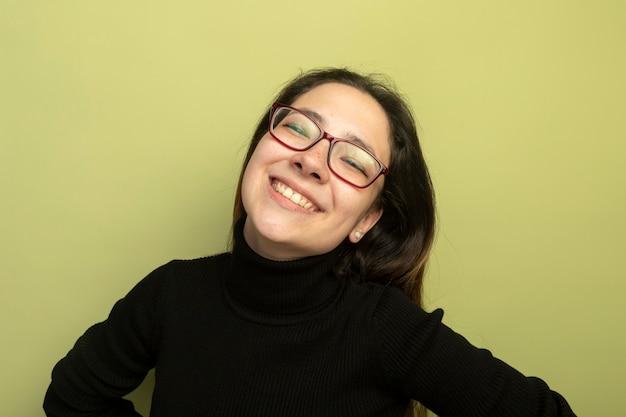 Mooi meisje in een zwarte coltrui en glazen kijken camera lachend met blij gezicht
