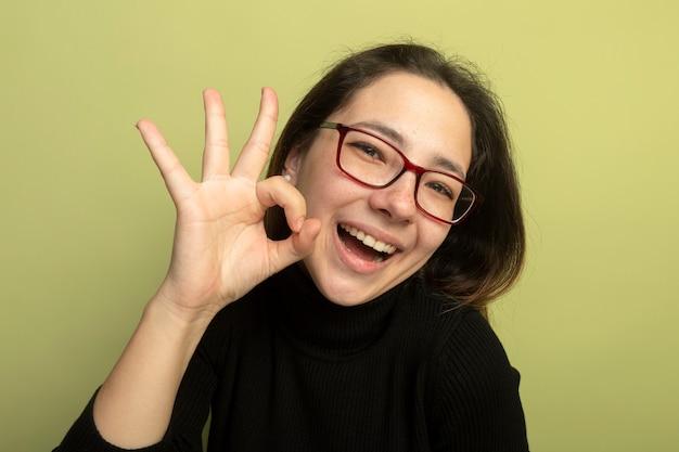 Mooi meisje in een zwarte coltrui en glazen lachend met blij gezicht ok teken tonen