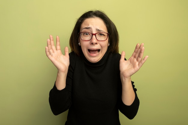 Mooi meisje in een zwarte coltrui en glazen schreeuwen met opgeheven handen wordt teleurgesteld