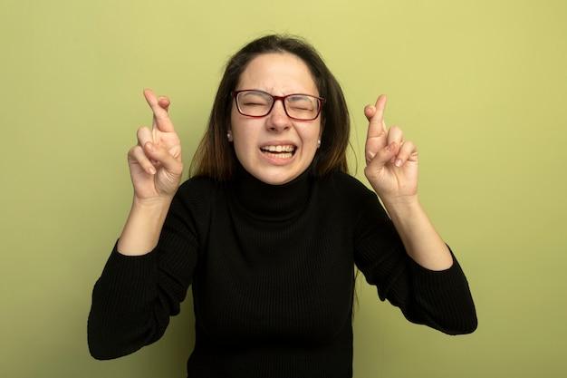 Mooi meisje in een zwarte coltrui en glazen wenselijke wens kruising vingers met hoop expressie met gesloten ogen maken