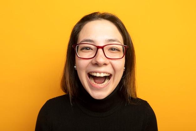 Mooi meisje in een zwarte coltrui lookign camera lachen uit