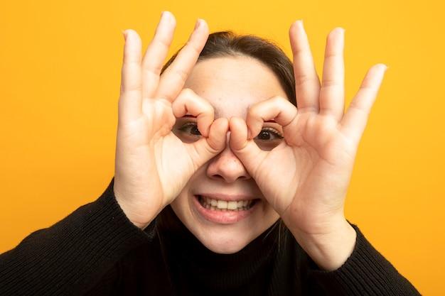 Mooi meisje in een zwarte coltrui ok teken als verrekijker met vingers door vingers glimlachend vrolijk maken
