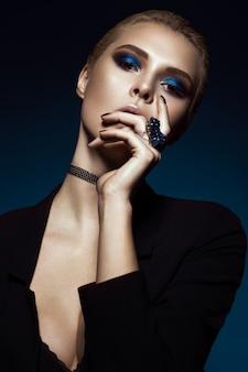 Mooi meisje in een zwarte jurk, steil haar en trendy make-up. glamour schoonheid gezicht.