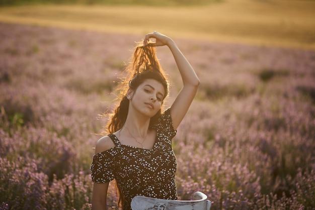 Mooi meisje in een zwarte jurk zit op een houten stoel en vormt in het midden van een lavendelveld.