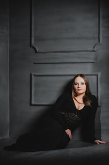 Mooi meisje in een zwarte lange jurk ligt