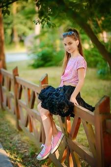 Mooi meisje in een zwarte prachtige tutu rok zit op een houten hek tussen groene bomen.
