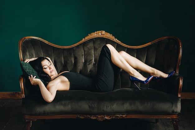 Mooi meisje in een zwarte strakke jurk en hakken. zwart lang golvend haar. oost-uiterlijk. bruine bank en groene muur.