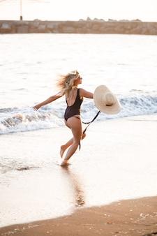 Mooi meisje in een zwarte zwembroek en hoed op een zandstrand aan zee in het zonlicht van de zonsondergang