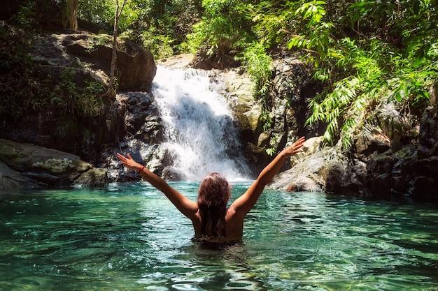 Mooi meisje in een zwembroek met open armen in de buurt van een waterval in een tropisch woud.
