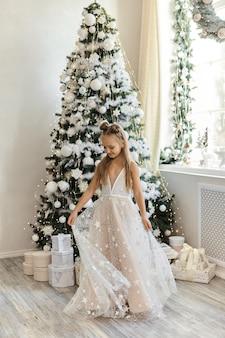 Mooi meisje in feestelijke jurk in kerst interieur