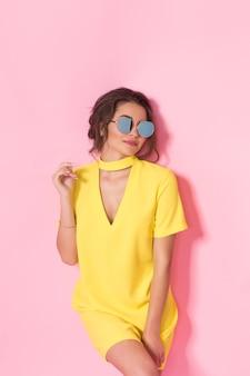 Mooi meisje in gele jurk dragen van een zonnebril poseren lachend op roze achtergrond