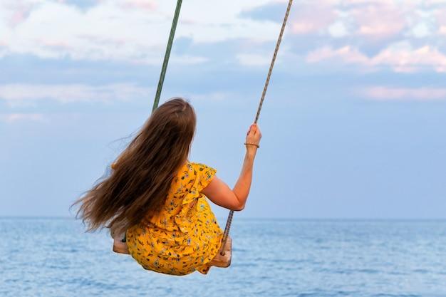 Mooi meisje in gele jurk met lang haar rijdt op schommel boven zee. achteraanzicht.