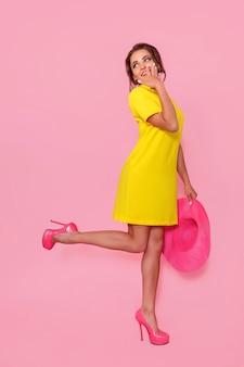 Mooi meisje in gele jurk met zonnebril poseren glimlachend op roze achtergrond in studio