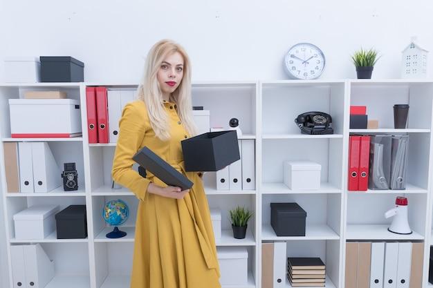 Mooi meisje in gele jurk op zoek naar documenten in zwarte doos