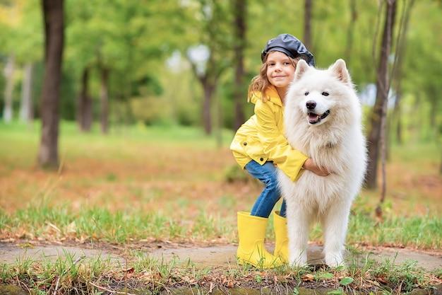 Mooi meisje in gele rubberen laarzen en regenjas op wandelingen, speelt met een mooie witte samojeed hond in het herfst park