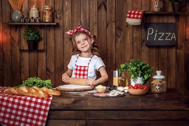 Mooi meisje in geruite schort die deeg voor pizza ontwikkelen