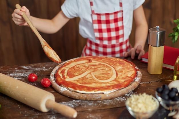 Mooi meisje in geruite schort kokende pizza, het verspreiden van saus met lepel in hartvorm