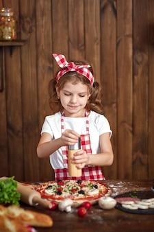 Mooi meisje in geruite schort kokende pizza