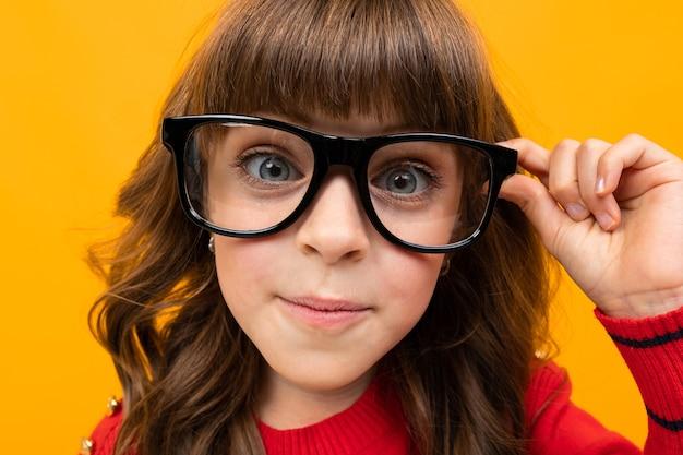 Mooi meisje in glazen close-up op een oranje studio achtergrond.