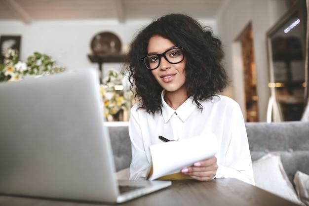 Mooi meisje in glazen die op laptop in restaurant werkt. jonge african american girl zit in café met laptop en notebook in de hand
