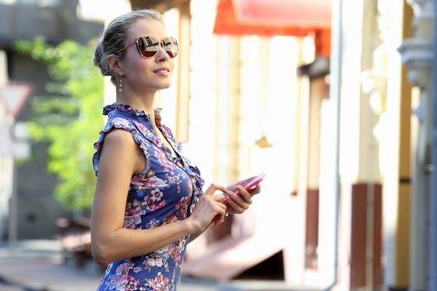 Mooi meisje in glazen met telefoon in de hand op zoek naar de kant