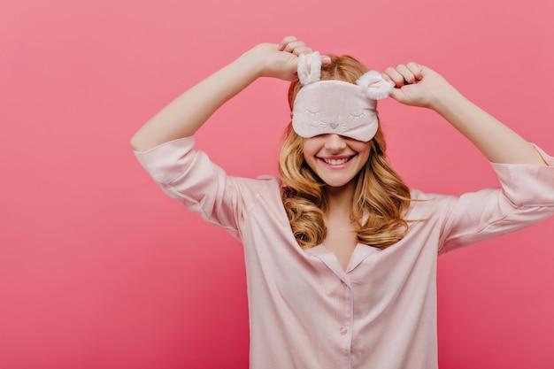 Mooi meisje in goed humeur gek rond voor het slapengaan. charmante krullende vrouw in oogmasker en nachtkleding lachend op roze muur.