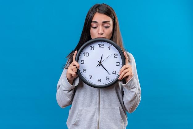 Mooi meisje in grijze hoody bedrijf klok en kijken met verwarring zicht naar klok staande over blauwe achtergrond