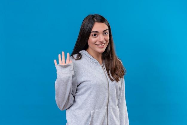 Mooi meisje in grijze hoody camera kijken met glimlach op gezicht en hallo gebaar permanent over blauwe achtergrond maken