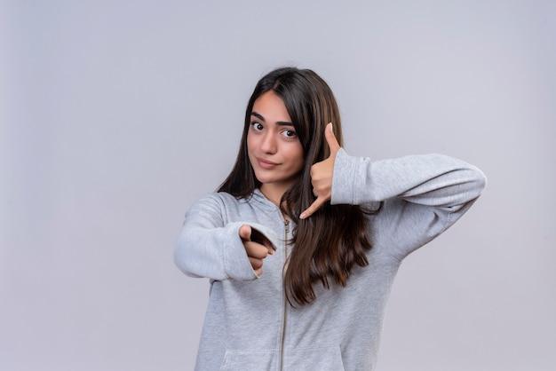 Mooi meisje in grijze hoody kijken camera serieus wijzend naar de camera bel me gebaar staande op witte achtergrond