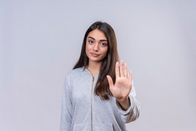 Mooi meisje in grijze hoody lookin op camera met onaangename uitdrukking stop gebaar permanent over witte achtergrond maken