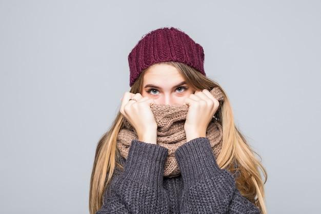 Mooi meisje in grijze trui en sjaal is koud op grijs