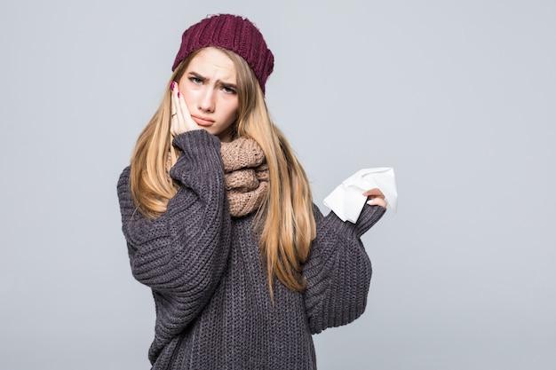 Mooi meisje in grijze trui heeft het koud en had griephoofdpijn op grijs