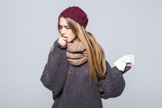 Mooi meisje in grijze trui is koud had griep hoest hoofdpijn op grijs