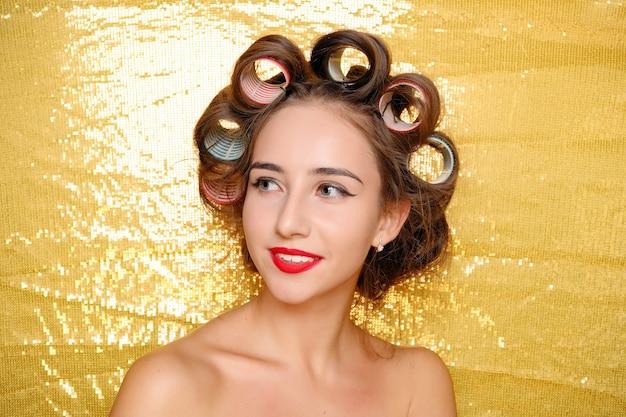 Mooi meisje in haarkrulspelden die op gouden background
