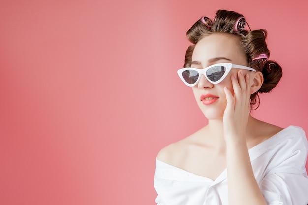 Mooi meisje in haarkrulspelden op roze muur.