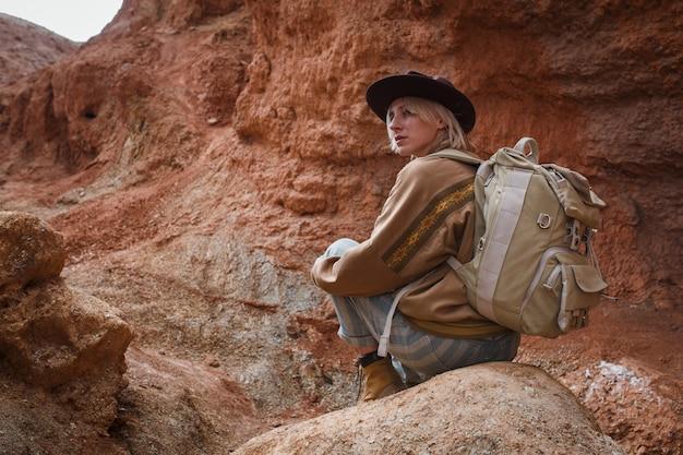 Mooi meisje in haas, hoed en met rugzak reist onder zand in het wild
