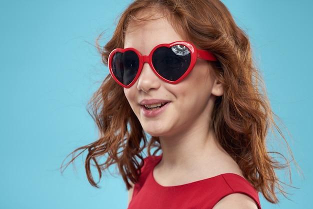 Mooi meisje in hart bril en een rode jurk, prinses, schattige baby op een blauwe ruimte