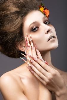 Mooi meisje in herfstbeeld met lange nagels met lichte en ongebruikelijke make-up. foto genomen in de studio op een grijze achtergrond