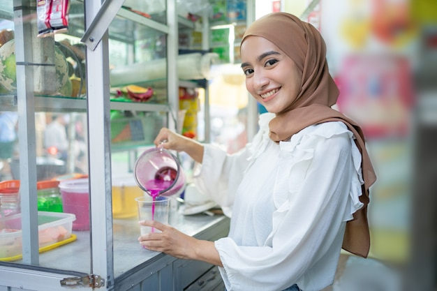 Mooi meisje in hijab glimlacht naar de camera die een blenderkan vasthoudt terwijl ze vruchtensap schenkt