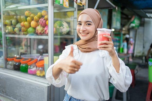 Mooi meisje in hijab glimlacht naar de camera met duimen omhoog terwijl ze een plastic beker vruchtensap vasthoudt