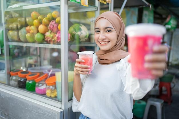 Mooi meisje in hijab glimlacht naar de camera terwijl ze een plastic beker vruchtensap vasthoudt