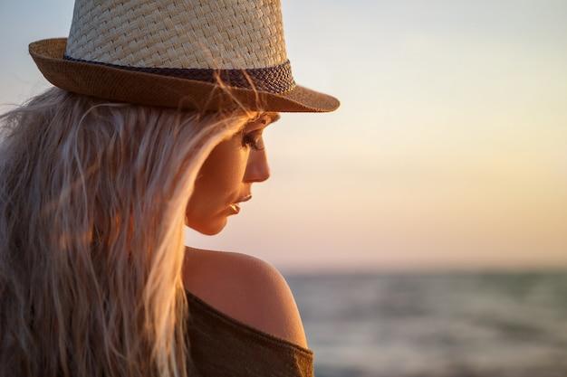 Mooi meisje in hoed door de zee bij zonsondergang.